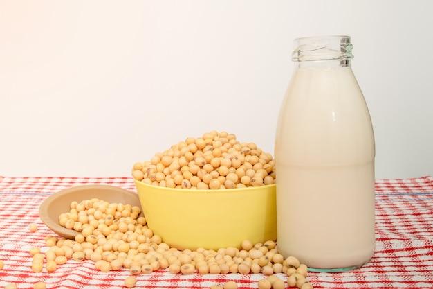 Mleko sojowe i ziarna soi w misce na czerwonym stole przed białym.