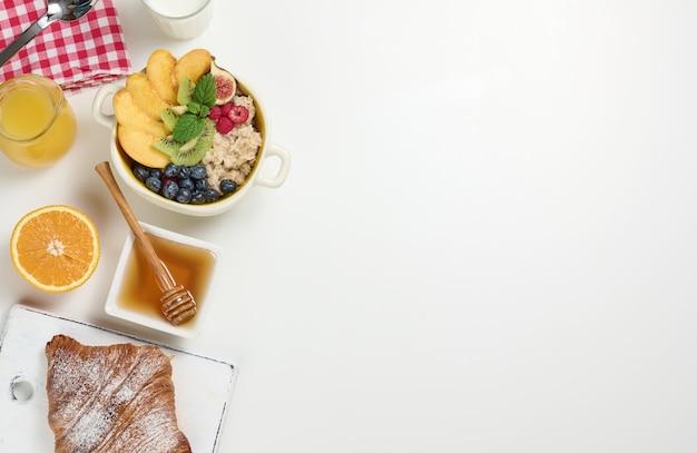 Mleko, talerz z owsianką i owocami, świeżo wyciśnięty sok w przezroczystej szklanej karafce, miód w misce na białym stole. zdrowe śniadanie, miejsce na kopię