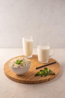 Mleko w filiżance, kefir w szklance i twarożek z ziołami w misce na drewnianej tacy na jasnym tle.