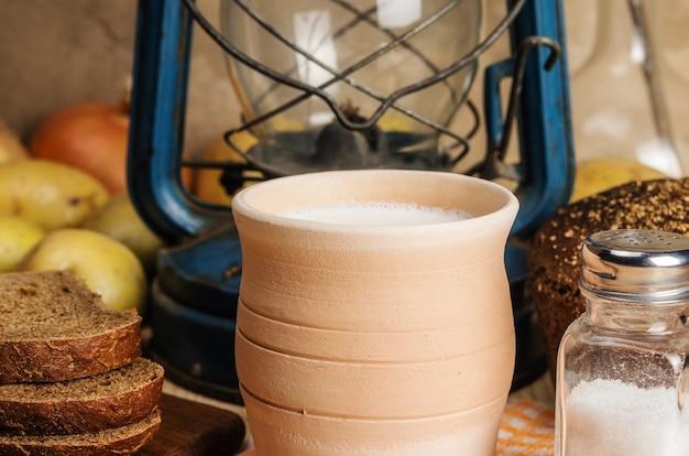 Mleko w naczyniu ceramicznym chleb żytni solniczka warzywa i nafta lampion na drewnianym stole
