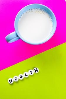 Mleko w niebieskiej filiżance i napis zdrowie wykonany z białych tabletek medycznych w kolorze jasnoróżowym i zielonym