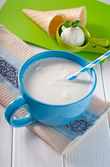 Mleko w niebieskim kubku ze słomką i gałką lodów