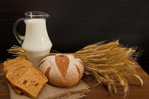 Mleko w przezroczystym dzbanku, okrągły i kwadratowy chleb żytni, snop na drewnianym stole, czarne tło, miejsce na tekst