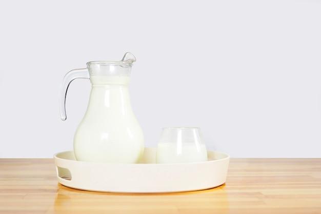 Mleko w szklance i dzbanku na drewnianym stole w okrągłej tacy na szarym tle. miejsce na kopię.