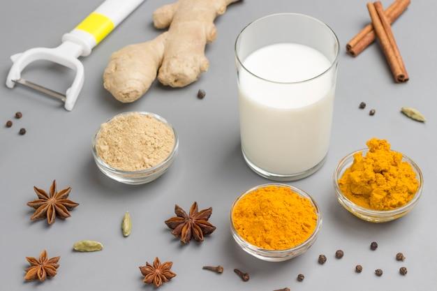 Mleko w szklance ze składnikami do gotowania indyjski napój z kurkumą