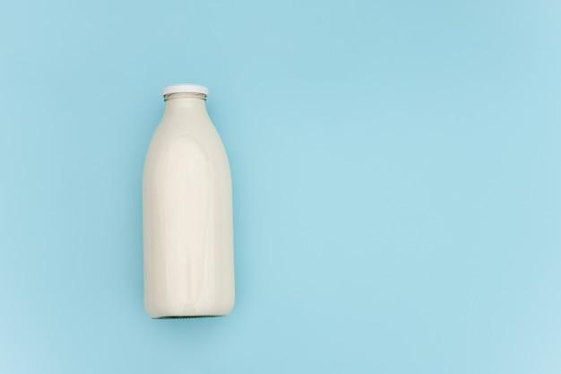 Mleko w szklanej butelce na błękitnym tle z kopii przestrzenią. leżał płasko widok z góry