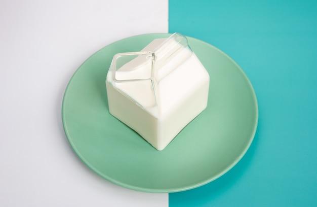 Mleko w szklanym dzbanku na mleko. na kolorowym tle i zielonym talerzu