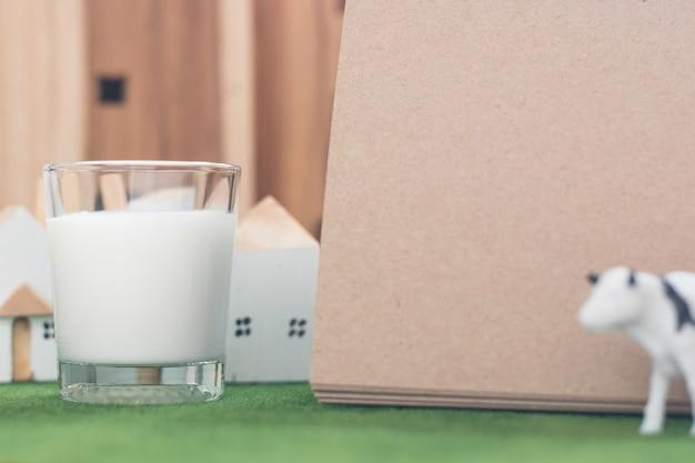 Mleko w szkle z pustą notatką papieru na trawie symulacji