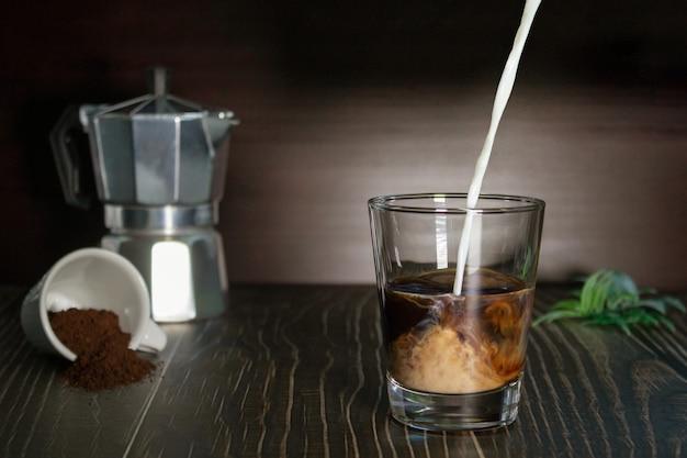 Mleko wlewa się do filiżanki kawy. selektywne skupienie