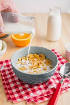 Mleko wlewa się do miski na płatki