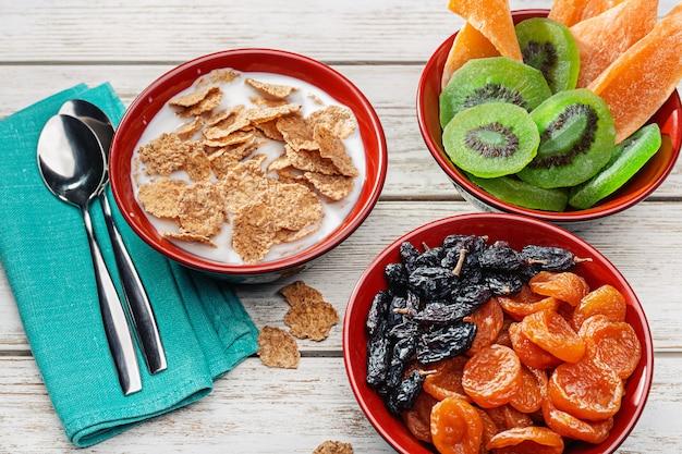 Mleko wlewa się do miski z płatkami. suszone kiwi, mango, morele i rodzynki, zdrowa żywność.
