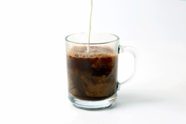 Mleko wlewa się do przezroczystej filiżanki czarnej kawy