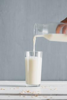 Mleko wlewa się do szklanki z butelką