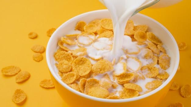 Mleko wlewanie do miski płatków kukurydzianych, widok z góry