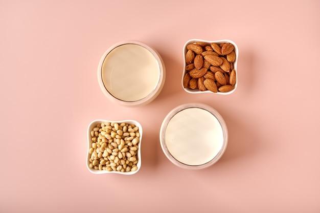 Mleko z migdałów i orzeszków pinii w szklankach selektywna ostrość i nasiona orzechów w miseczkach na różowym proszku