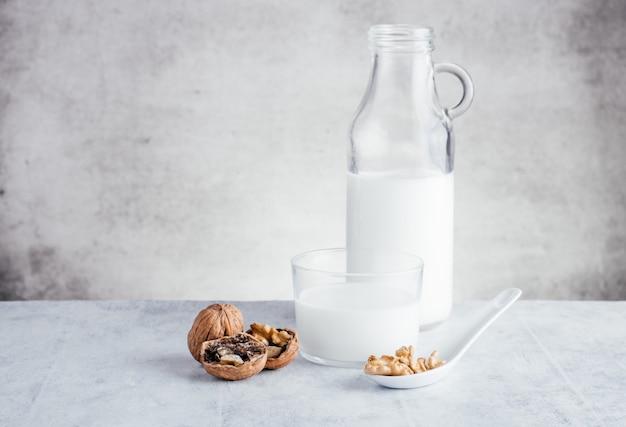 Mleko z orzechów warzywnych i kawałki orzecha włoskiego na łyżce