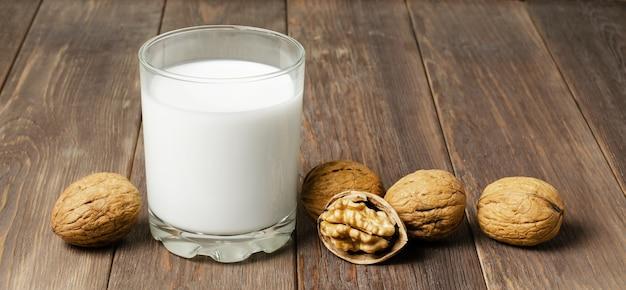 Mleko z orzechów włoskich i orzechów na brązowym tle drewnianych. produkty zawierające białko roślinne, witaminy i przydatne aminokwasy. skopiuj miejsce
