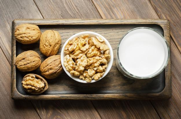 Mleko z orzechów włoskich i orzechów na brązowym tle drewnianych. produkty zawierające białko roślinne, witaminy i przydatne aminokwasy.