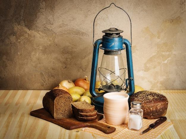 Mleko żytnie chleb deska do krojenia sól cebula ziemniaki nóż i nafta latarnia na drewnianym stole