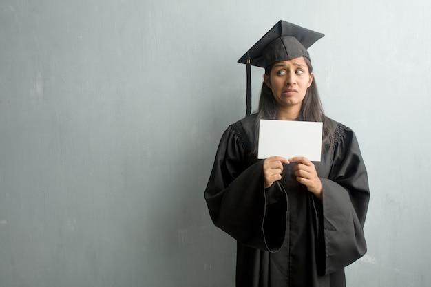Młoda absolwentka indyjskiej kobiety na ścianie bardzo przestraszona i przestraszona, rozpaczliwie czegoś pragnąca, krzyki cierpienia i otwarte oczy, koncepcja szaleństwa. trzymając afisz.