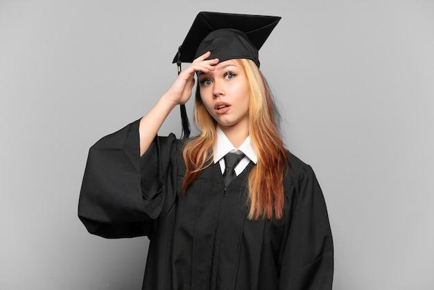Młoda absolwentka uniwersytetu dziewczyna na białym tle robi gest zaskoczenia, patrząc w bok
