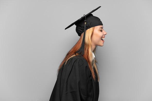 Młoda absolwentka uniwersytetu dziewczyna na białym tle śmiejąca się w pozycji bocznej