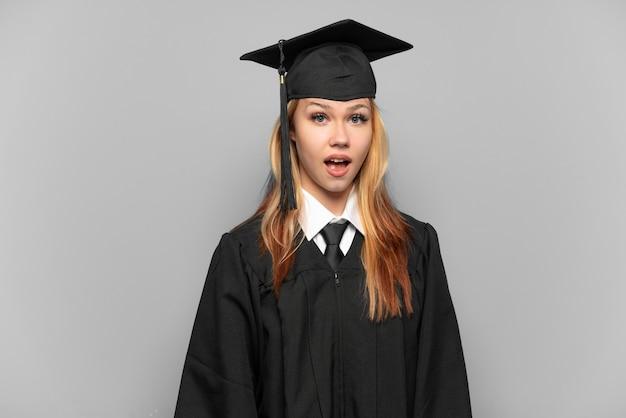 Młoda absolwentka uniwersytetu dziewczyna na białym tle z niespodzianką wyrazem twarzy