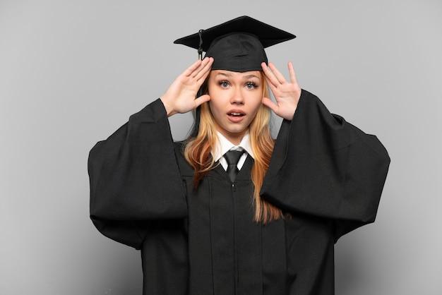 Młoda absolwentka uniwersytetu dziewczyna na białym tle z wyrazem zaskoczenia