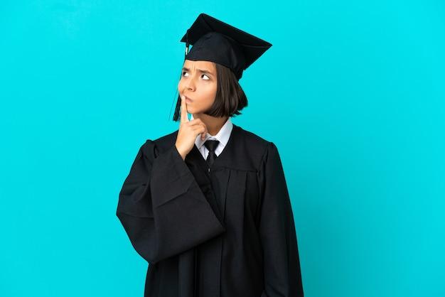Młoda absolwentka uniwersytetu dziewczyna na odosobnionym niebieskim tle, mająca wątpliwości podczas patrzenia w górę