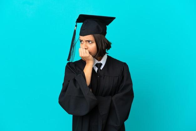 Młoda absolwentka uniwersytetu dziewczyna na odosobnionym niebieskim tle, mająca wątpliwości