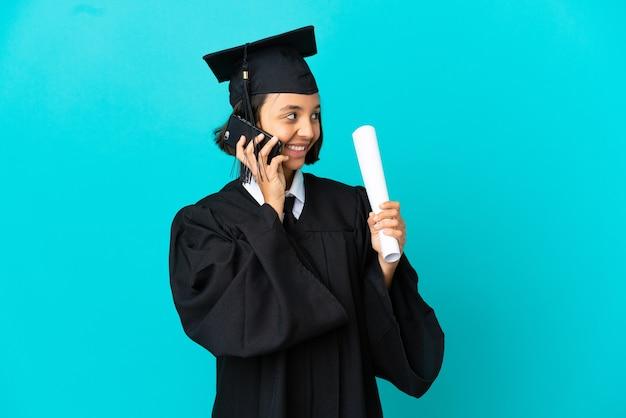 Młoda absolwentka uniwersytetu dziewczyna na odosobnionym niebieskim tle, prowadząca rozmowę z telefonem komórkowym z kimś