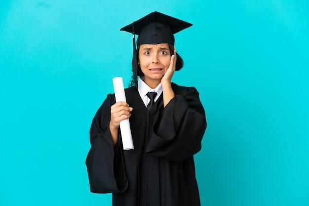 Młoda absolwentka uniwersytetu dziewczyna na odosobnionym niebieskim tle robi nerwowy gest