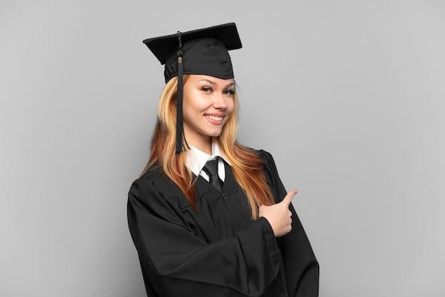 Młoda absolwentka uniwersytetu dziewczyna wskazująca tyłem na białym tle