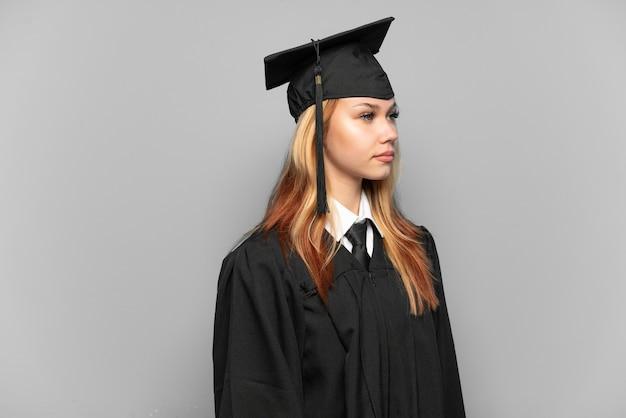 Młoda absolwentka uniwersytetu na białym tle, patrząc w bok