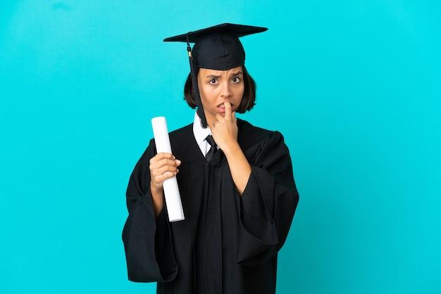 Młoda absolwentka uniwersytetu na odosobnionym niebieskim tle nerwowa i przestraszona