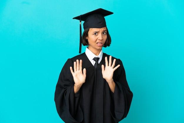 Młoda absolwentka uniwersytetu na odosobnionym niebieskim tle nerwowe rozciąganie rąk do przodu