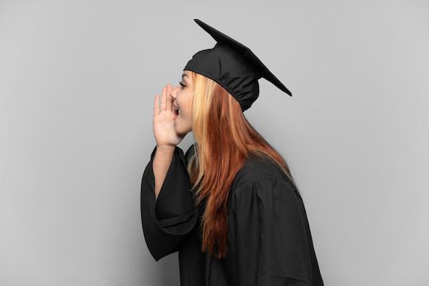 Młoda absolwentka uniwersytetu na odosobnionym tle krzyczy z szeroko otwartymi ustami