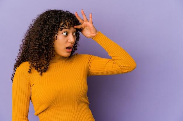 Młoda african american afro kobieta na białym tle patrząc daleko, trzymając rękę na czole.