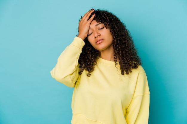 Młoda african american afro kobieta na białym tle zmęczony i bardzo senny, trzymając rękę na głowie.