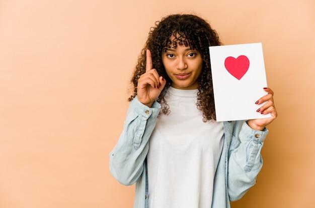 Młoda african american afro kobieta trzyma kartę walentynki pokazując numer jeden z palcem.