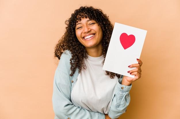 Młoda african american afro kobieta trzyma kartę walentynki śmiejąc się i zabawy.