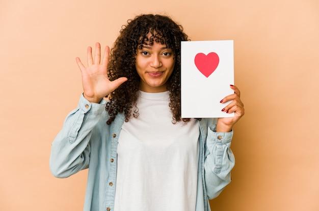 Młoda african american afro kobieta trzyma kartę walentynki uśmiechnięty wesoły pokazując numer pięć palcami.