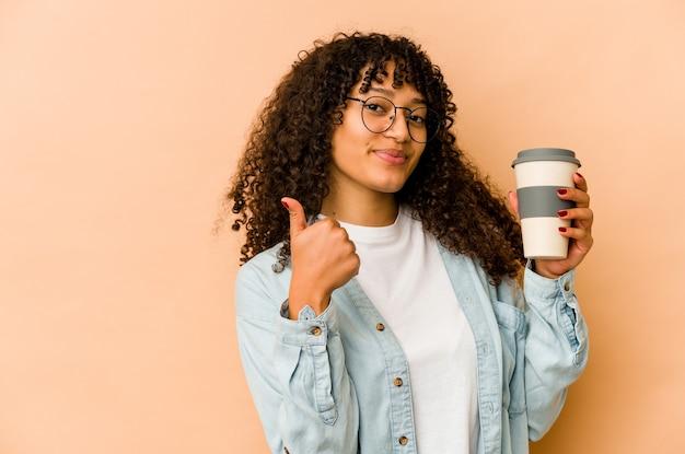 Młoda african american afro kobieta trzyma kawę na wynos, uśmiechając się i podnosząc kciuk do góry