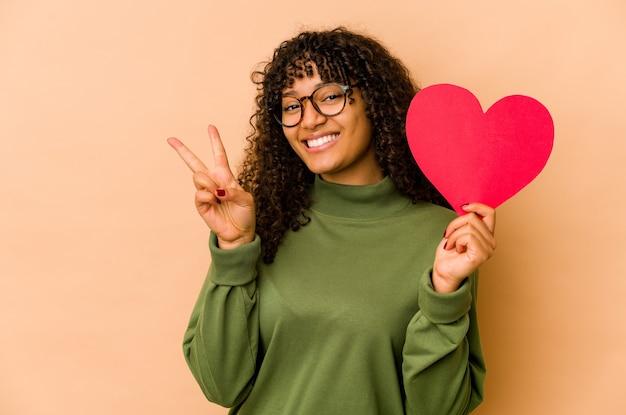 Młoda african american afro kobieta trzyma serce walentynki wyświetlono numer dwa palcami.