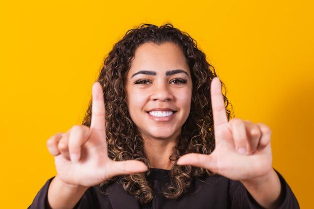 Młoda african american dziewczyna nosi ubrania wykonawcze uśmiechając się, co ramka na zdjęcia z rękami i palcami z uśmiechniętą twarz. koncepcja kreatywności i fotografii.