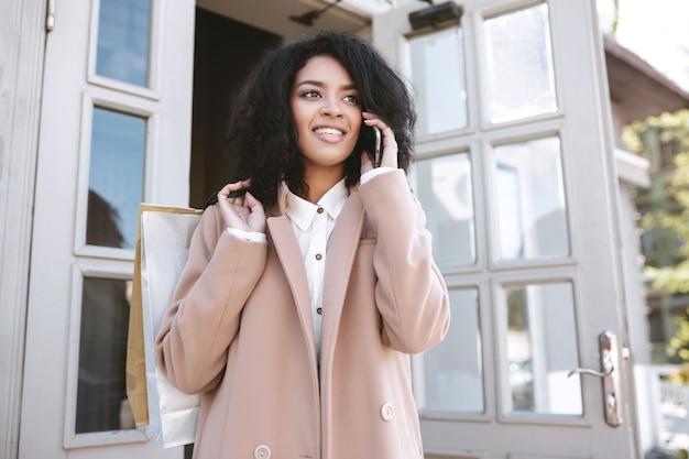 Młoda african american girl stojąca z telefonem i paczkami w ręce bardzo uśmiechnięta dziewczyna w płaszczu rozmawia przez telefon komórkowy portret pięknej pani z ciemnymi kręconymi włosami i telefonem komórkowym w dłoni