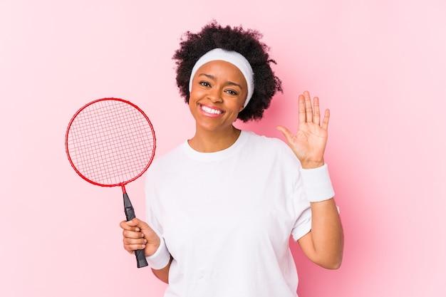 Młoda african american kobieta gra w badmintona na białym tle uśmiechnięty wesoły pokazując numer pięć palcami.