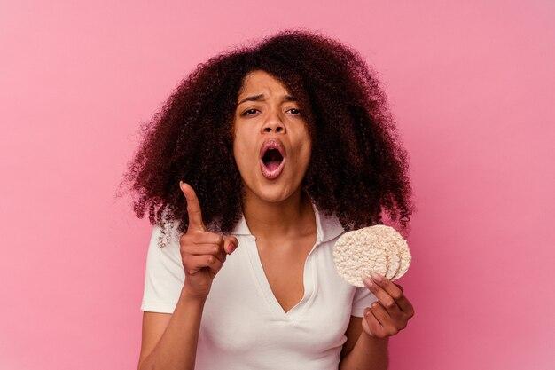 Młoda african american kobieta jedzenie ciastek ryżowych na różowym tle, mając pomysł, koncepcja inspiracji.