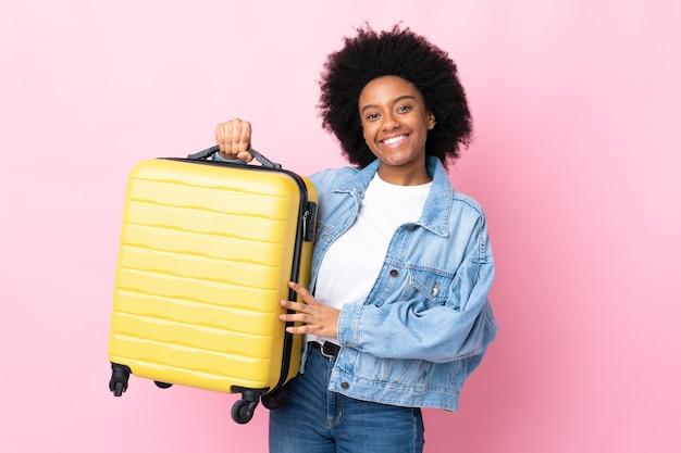 Młoda african american kobieta odizolowywająca z walizką podróżną