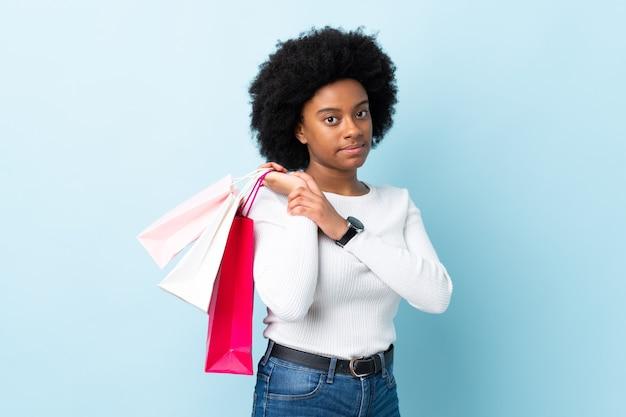 Młoda african american kobieta samodzielnie na niebiesko trzymając torby na zakupy